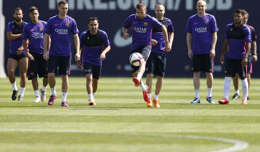 FC Barcelona's Jordi Alba, center, controls the ball with his teammates during a training session at the Sports Center FC Barcelona Joan Gamper in San Joan Despi, Spain, Friday, May 29, 2015.  FC Barcelona will play against Athletic Bilbao in the Spanish Copa del Rey soccer final on Saturday May 30. (AP Photo/Manu Fernandez)