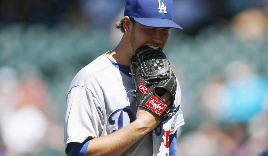 Los Angeles Dodgers relief pitcher Ian Thomas bites his glove after retiring the Colorado Rockies in the bottom of the fifth inning but yielding two runs in the first baseball game of a doubleheader, Tuesday, June 2, 2015, in Denver. (AP Photo/David Zalubowski)