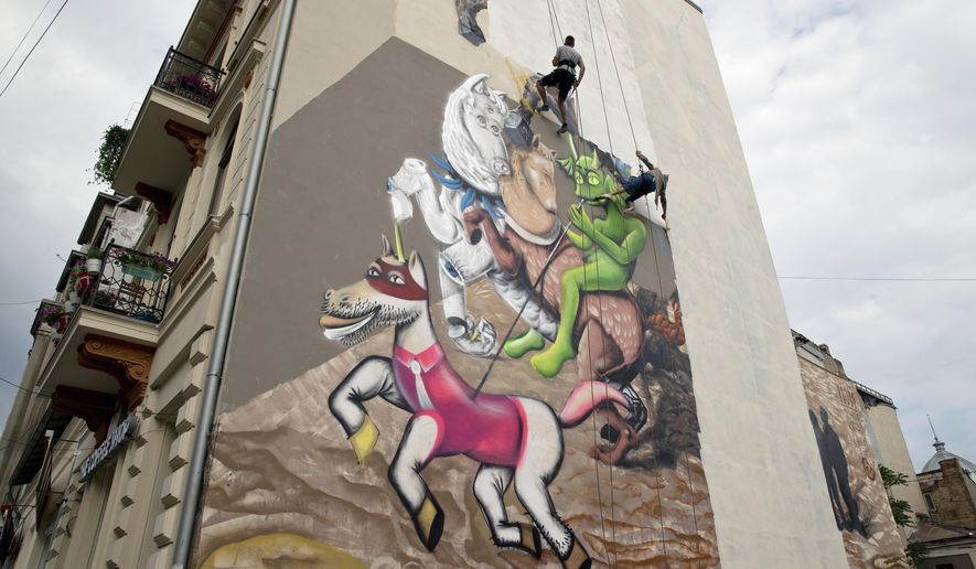In this photo taken May 8, 2015, workers paint over a mural depicting St. George in downtown Bucharest, Romania. When a gigantic mural of St. George appeared next to a historic church dedicated to the revered figure, many hailed it as a brilliant piece of street art but the influential Romanian Orthodox Church was not amused and the surreal interpretation painted just yards from the 18th century church - triggering outrage from priests and pious residents was painted over days later. (AP Photo/Vadim Ghirda)