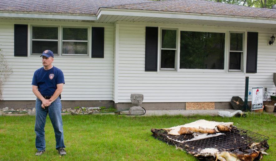 Muskegon Twp. Fire Chief, Dave Glotzbach talks about fire safety and the importance of smoke detectors Friday, May 29, 2015 at a home in the 1900 block of Riegler Road, where two people died in a fatal fire around 2:30 a.m. in Muskegon Twp., Mich. Glotzbach says a 64-year-old woman and her 36-year-old son died in the fire, which started about 2:30 a.m. Friday in the basement of the home. (Joel Bissell/The Muskegon Chronicle via AP) ALL LOCAL TELEVISION OUT; LOCAL TELEVISION INTERNET OUT