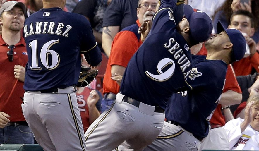 Milwaukee Brewers shortstop Jean Segura (9) fails to catch a foul ball by St. Louis Cardinals' Matt Carpenter, between third baseman Aramis Ramirez (16) and left fielder Gerardo Parra during the fourth inning of a baseball game Tuesday, June 2, 2015, in St. Louis. (AP Photo/Jeff Roberson)