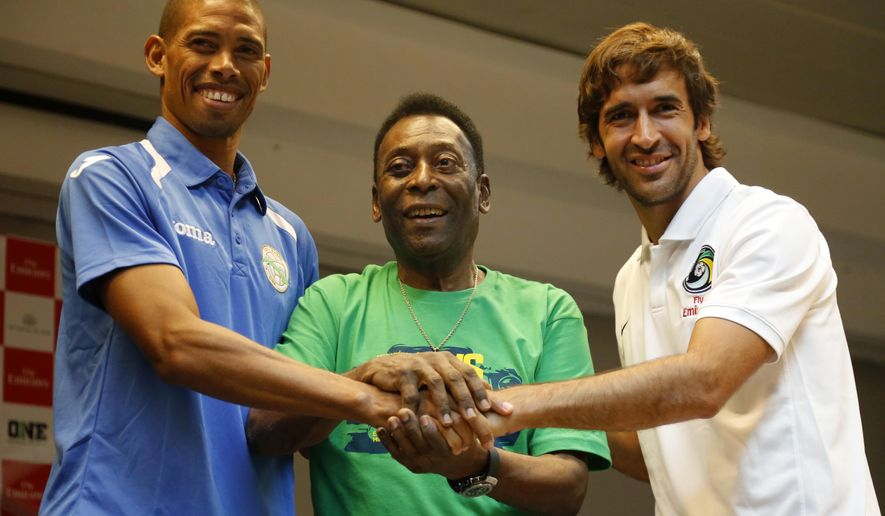 Cuba's national team captain Yenier Marquez, left, legendary New York Cosmos and Brazilian national soccer team player Pele and Cosmos player Raul Gonzalez, right, join hands during a press conference ahead of their friendly soccer match in Havana, Cuba, Monday, June 1, 2015. While the two governments have yet to reopen embassies after nearly half a year of complicated negotiations, Havana has been flooded by a surge of U.S. tourists, as well as delegations of lawmakers, businesspeople and athletes. (AP Photo/Desmond Boylan)