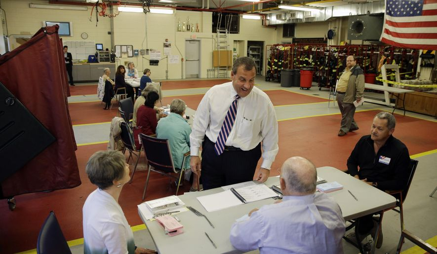 New Jersey Gov. Chris Christie, center, talks with election workers as he prepares to vote Tuesday, June 2, 2015, in Mendham Township, N.J. A quiet primary season will wrap up as New Jersey voters head to the polls to pick Democratic and Republican candidates for November's Assembly election. The Assembly is atop the ticket for the first time in 16 years because of a quirk in term lengths, and in 35 of the state's 40 districts the primaries are not contested. (AP Photo/Mel Evans)