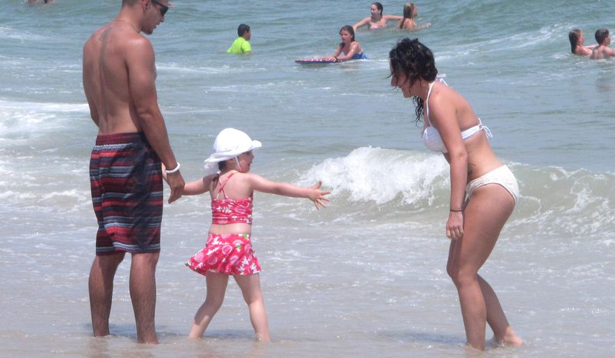 This June 30, 2014 photo shows a family playing in the surf in Ship Bottom, N.J. on Long Beach Island. A scientific study of sea level rise is due to begin blasting the ocean floor off Long Beach Island with sound waves on Wednesday June 3, 2015, drawing opposition from environmentalists who fear it may harm marine animals including dolphins and turtles. (AP Photo/Wayne Parry)