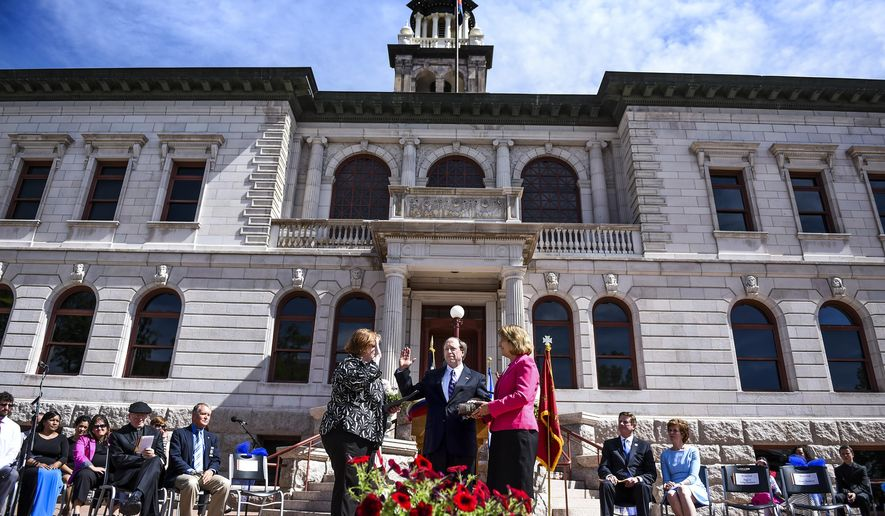 John Suthers, center, stands with his wife, Janet Suthers, as he is sworn in as Colorado Springs' 41st mayor by City Clerk Sarah Johnson during a ceremony Tuesday, June 2, 2015 at the Pioneers Museum in Colorado Springs, Colo. (Michael Ciaglo/The Gazette via AP) MAGS OUT; MANDATORY CREDIT