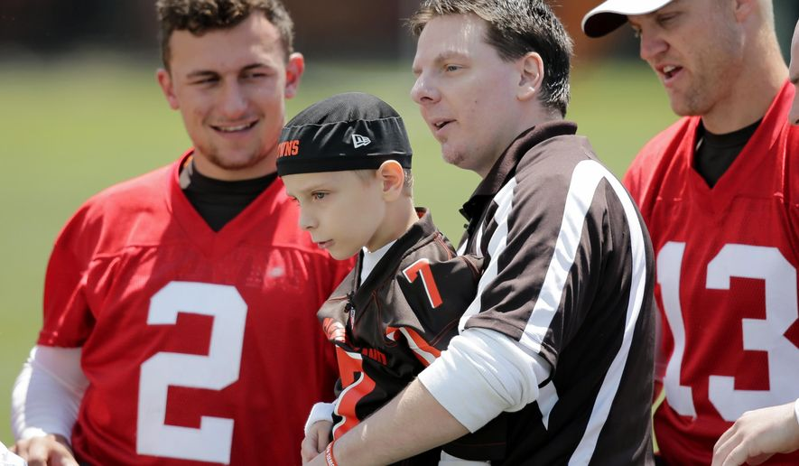 Cleveland Browns quarterbacks Johnny Manziel (2) and Josh McCown (13) spend time with Dylan Sutcliffe, 9, and his dad, Derek, during an NFL football organized team activity, Tuesday, June 2, 2015, in Berea, Ohio. Sutcliffe signed a contract with the Browns after he told Make-A-Wish that his dream was to play football for the team. (AP Photo/Tony Dejak)