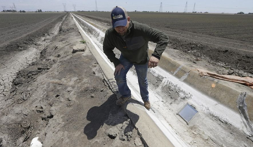 FILE - Ihis Monday, May 18, 2015, file photo, farmer Gino Celli climbs out of a irrigation canal that is covered in dried salt on a field he farms near Stockton, Calif. Moving to meet voluntary water conservation targets, dozens of farmers in the Sacramento-San Joaquin River Delta submitted plans Monday, June 1 to the state saying they intend to plant less thirsty crops and leave some fields unplanted amid the relentless California drought, officials said. (AP Photo/Rich Pedroncelli,File)