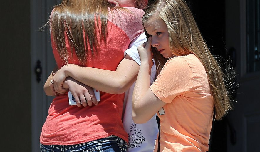 Kiana Stoker, center, sister to boating accident survivor Tiffany Stoker, gets support from friends in Harrisville, Utah, Tuesday, June 2, 2015. Authorities say the people killed when a boat capsized on a Utah lake were a man, two of his daughters and one of their friends.(Ravell Call/The Deseret News via AP)  SALT LAKE TRIBUNE OUT;  MAGS OUT