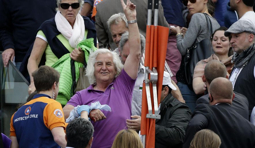 An unidentified slightly injured spectator waves after a metal paneling fell on center court while France's Jo-Wilfried Tsonga played Japan's Kei Nishikori during their quarterfinal match of the French Open tennis tournament at the Roland Garros stadium, Tuesday, June 2, 2015 in Paris, France. French Open organizers say three people were slightly injured by the falling piece of metal paneling that detached in strong winds from a giant TV screen overlooking center court and crashed onto spectators below. (AP Photo/Thibault Camus)