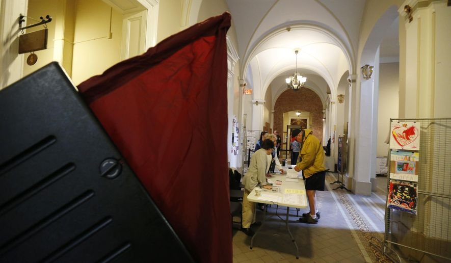 Walter Murawinski, right, is helped by poll workers Ira Landgarten, left, and JoAnn Bauer, center, as he figures out where his polling place is for the Hudson County primary election Hoboken City Hall, Tuesday, June 2, 2015, in Jersey City, N.J. (AP Photo/Julio Cortez)