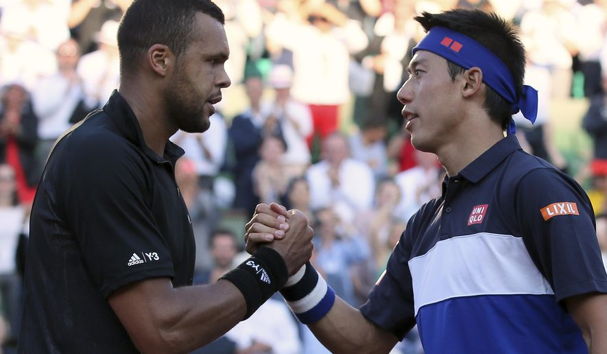 France's Jo-Wilfried Tsonga shakes hands with Japan's Kei Nishikori after winning in the quarterfinal match of the French Open tennis tournament in five sets 6-1, 6-4, 4-6, 3-6, 6-3, at the Roland Garros stadium, in Paris, France, Tuesday, June 2, 2015. (AP Photo/David Vincent)