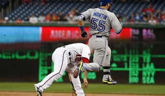 Toronto Blue Jays' Russell Martin (55) is safe at first base as Washington Nationals first baseman Tyler Moore can't get to the throw from third baseman Yunel Escobar during the first inning of the second baseball game of a doubleheader at Nationals Park, Tuesday, June 2, 2015, in Washington. (AP Photo/Alex Brandon)