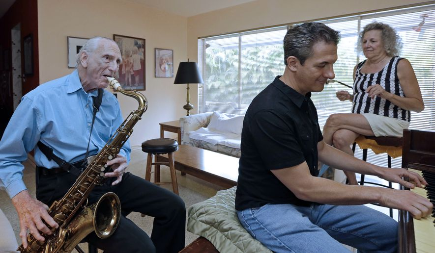 In this May 11, 2015 photo, Al Karp, left, plays the saxophone as he rehearses with his son, Larry, and wife Saundra, right, at their home in North Miami Beach, Fla. The trio performs old standards locally as the Karp Family to ease stress and help raise money to save their home from foreclosure. (AP Photo/Alan Diaz)