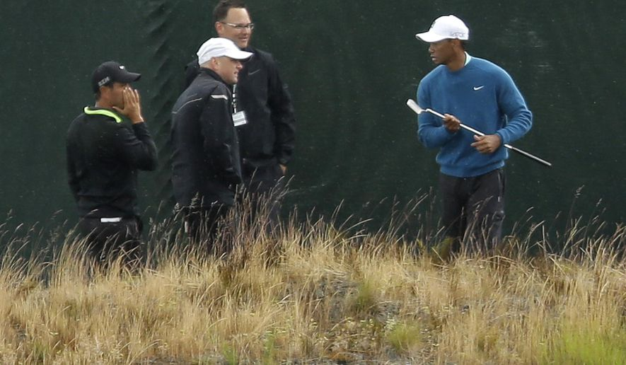 Golfer Tiger Woods, right, walks past a fence as rain begins to fall, Tuesday, June 2, 2015, as he took practice shots at Chambers Bay in University Place, Wash., where the U.S. Open will be played June 18-21, 2015. (AP Photo/Ted S. Warren)