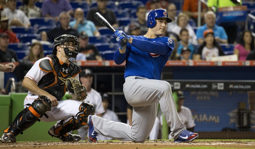 Miami Marlins catcher J.T. Realmuto (20) and Chicago Cubs Anthony Rizzo (44) watch as he hits a double during the third inning of a baseball game in Miami, Tuesday, June 2, 2015. (AP Photo/J Pat Carter)