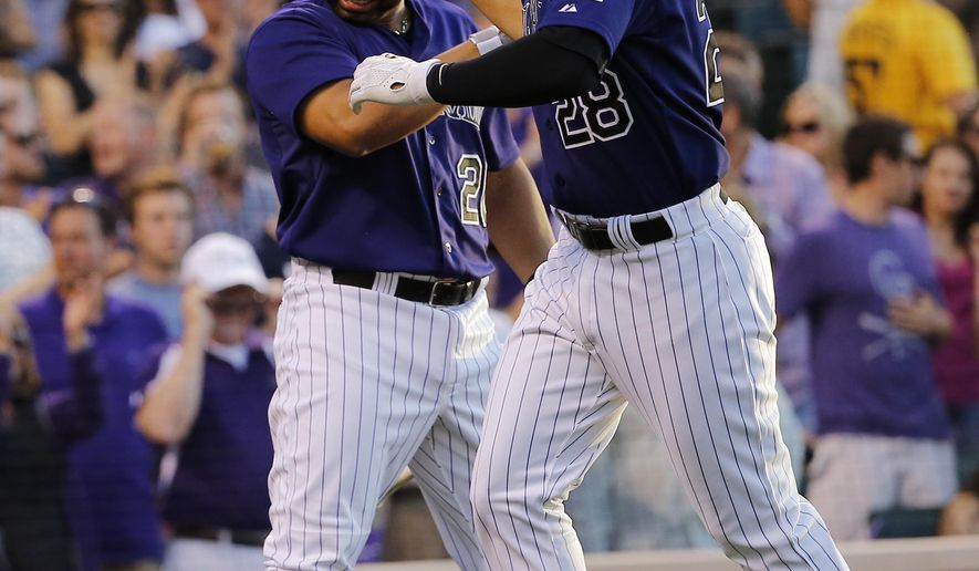 Colorado Rockies' Nolan Arenado celebrates a two run home run against the Los Angeles Dodgers with teammate Wilin Rosario (20) during the fourth inning of a baseball game Monday, June 1, 2015, in Denver. (AP Photo/Jack Dempsey)