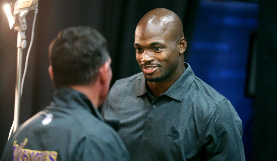 Viking head coach Mike Zimmer, left, and running back Adrian Peterson smile at each other before Peterson spoke to the media during a press conference at Winter Park Monday June 2, 2015 in Eden Prairie, Minn., Tuesday June 2, 2015.  Peterson practiced with the Vikings for the first time in nine months on Tuesday.   (Jerry Holt/Star Tribune via AP)  MANDATORY CREDIT; ST. PAUL PIONEER PRESS OUT; MAGS OUT; TWIN CITIES LOCAL TELEVISION OUT