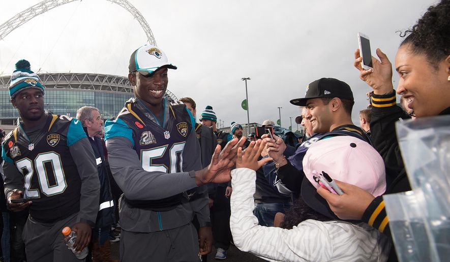 FILE - In this November, 2014, file photo, Jacksonville Jaguars linebacker Telvin Smith, center, greets fans as he arrives during the NFL Fan Rally outside Wembley Stadium in London, before a football game against the Dallas Cowboys. NFL Commissioner Roger Goodell said the NFL is interested in adding more international games in Germany, Mexico and Brazil. (AP Photo/Tim Ireland, File)
