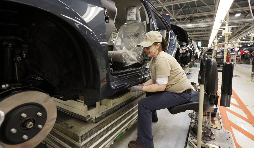 In this Feb. 12, 2015 photo, a technician adjusts the molding on a new Corolla at the Toyota Motor Manufacturing plant in Blue Springs, Miss. Automakers release vehicle sales for May 2015 on Tuesday, June 2, 2015. (AP Photo/Rogelio V. Solis)