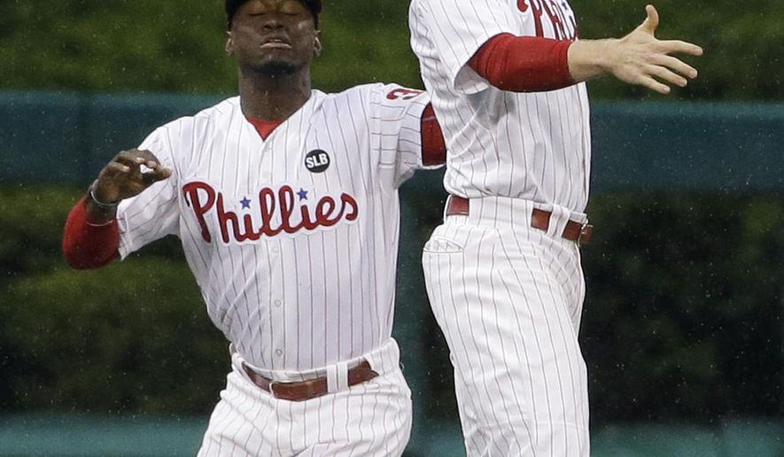 Philadelphia Phillies left fielder Cody Asche, right, catches a fly out by Cincinnati Reds' Brayan Pena as center fielder Odubel Herrera charges in during the first inning of a baseball game, Tuesday, June 2, 2015, in Philadelphia. (AP Photo/Matt Slocum)