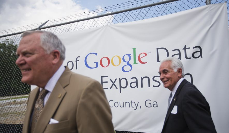 A banner hangs on the fence at the site of a proposed $300 million expansion of Google's data center operations as Georgia Gov. Nathan Deal, left, and Douglas County Commissioner Tom Worthan, right, take a tour Tuesday, June 2, 2015, in Lithia Springs, Ga. The new facility will be located next to the existing data center, one of 13 in the world, and will add 25 jobs to the 350 employees currently employed there by Google. The new facility is scheduled to be operational by the end of 2016. (AP Photo/David Goldman)