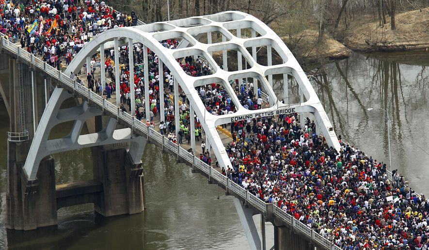 FILE- In this In this March 8, 2015, file photo, crowds of people move in a symbolic walk across the Edmund Pettus Bridge in Selma, Ala.  Alabama senators on Wednesday, June 3 approved a resolution to rename the bridge the Journey to Freedom Bridge. The bridge became a symbol of the fight for voting rights after marchers were beaten by state troopers on the bridge on March 7, 1965. (AP Photo/Butch Dill, File)