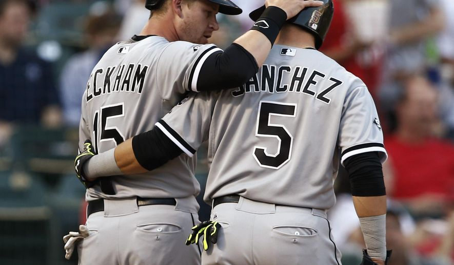 Chicago White Sox's Gordon Beckham (15) and Carlos Sanchez congratulate each other after scoring on a double by Adam Eaton against the Texas Rangers during the second inning of a baseball game, Wednesday, June 3, 2015, in Arlington, Texas. (AP Photo/Jim Cowsert)