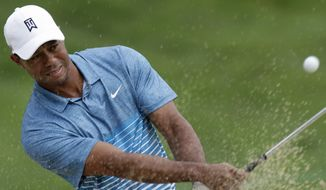 Tiger Woods hits from the sand on the 18th hole during a practice round for The Memorial golf tournament, Wednesday, June 3, 2015, in Dublin, Ohio. (AP Photo/Jay LaPrete)