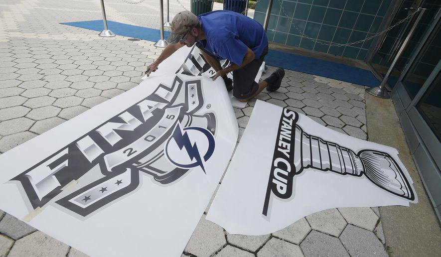 Bill Gaw puts up a logo outside the arena before Game 1 of the NHL hockey Stanley Cup Final between the Tampa Bay Lightning and the Chicago Blackhawks in Tampa, Fla., Wednesday, June 3, 2015.  (AP Photo/Phelan M. Ebenhack)