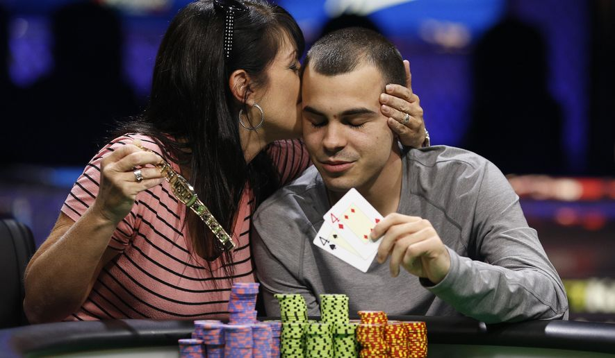 Lance Garcia gets a kiss from his mother, Kristen Scott, while posing for photographers after he won the World Series of Poker Colossus event Wednesday, June 3, 2015, in Las Vegas. (AP Photo/John Locher)