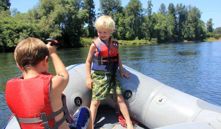 In this July 2014 photo, Rylan and Noah Peters sit in a raft on a float between Spring Valley and Grand Island on the Willamette River near Salem, Ore. (Zach Urness/Statesman-Journal via AP)