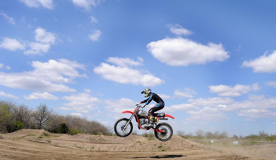 In this April 26, 2015, photo, Derek Devine jumps his vintage motocross bike on the trail he has built behind his home in rural Buckingham, Ill. Devine, 23, has won back-to-back American Motorcycle Association Vintage Motocross Championships. Working with his father, Rick, a former rider and a talented cycle builder, Derek not only won the 2013 title, he won every race on the circuit. He came back last year and while he failed to pull off another clean sweep, he easily won the season point standings. (Mike Voss/The Daily Journal via AP)