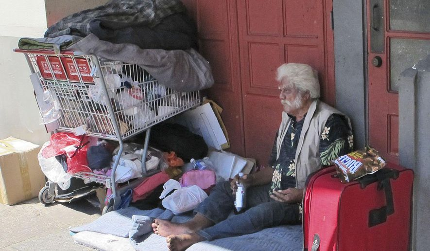 In this photo made on Tuesday, June 2, 2015, a homeless man sits on a sidewalk in Chinatown in Honolulu, Hawaii. The Honolulu City Council is considering several bills that would expand the ban on sitting and lying down on sidewalks in commercial districts. The prohibition began in Waikiki and has been extended to a growing list of neighborhoods on Oahu. (AP Photo/ Cathy Bussewitz)