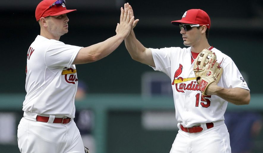 St. Louis Cardinals' Matt Holliday, left, and Randal Grichuk celebrate after the Cardinals' 7-4 victory over the Milwaukee Brewers in a baseball game Wednesday, June 3, 2015, in St. Louis. (AP Photo/Jeff Roberson)