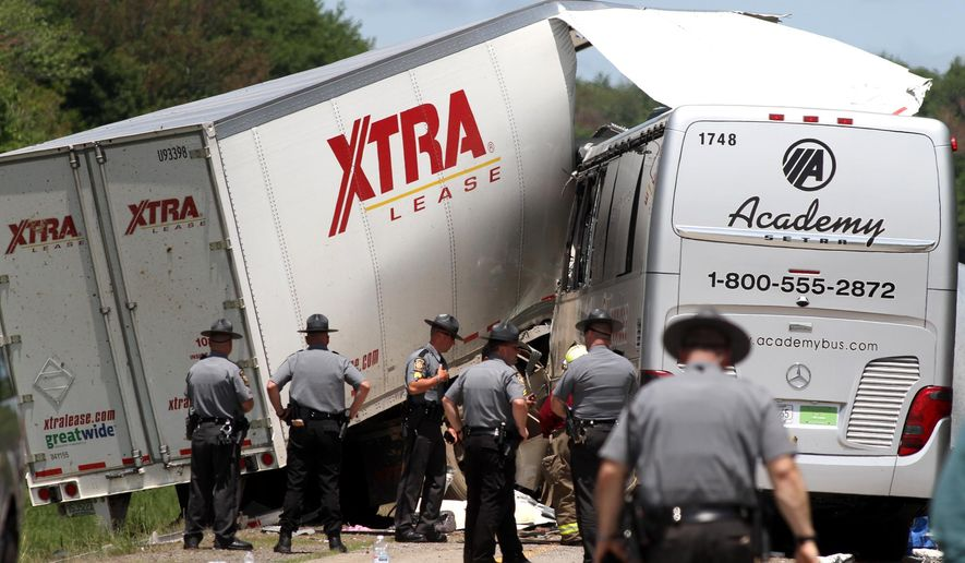 Authorities investigate the scene of a fatal collision between a tractor-trailer and a tour bus on Interstate 380 near Tobyhanna, Pa., Wednesday, June 3, 2015. Multiple people were killed and more than a dozen were sent to hospitals. (Jake Danna Stevens/The Times & Tribune via AP)