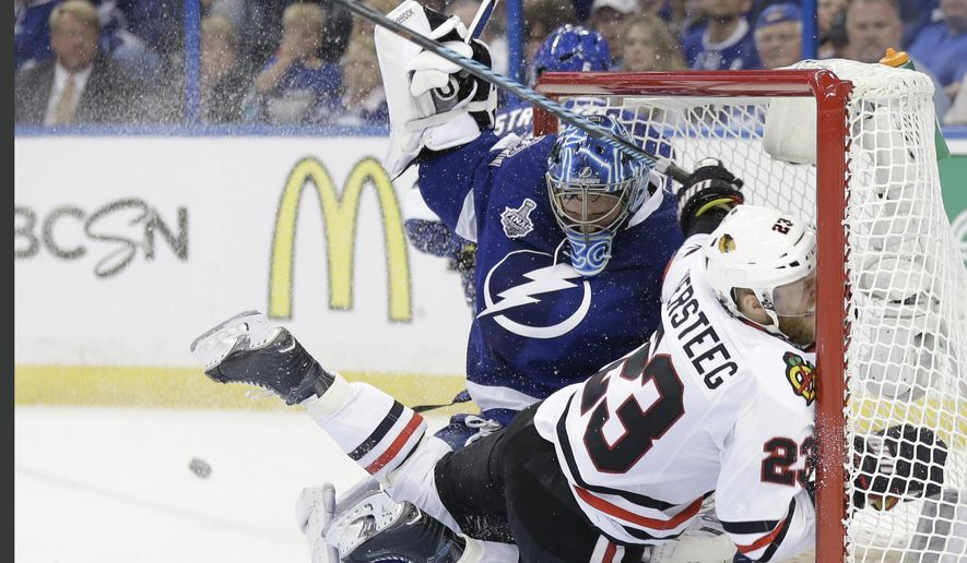 Chicago Blackhawks right wing Kris Versteeg (23) of Canada, collides with Tampa Bay Lightning goalie Ben Bishop (30) during the second period in Game 1 of the NHL hockey Stanley Cup Final in Tampa, Fla., Wednesday, June 3, 2015.  (AP Photo/Chris O' Meara)