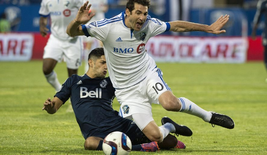 Montreal Impact's Ignacio Piatti is tripped by Vancouver Whitecaps' Matias Laba during the first half of an MLS soccer game, Wednesday, June 3, 2015, in Montreal. (Paul Chiasson/The Canadian Press via AP)