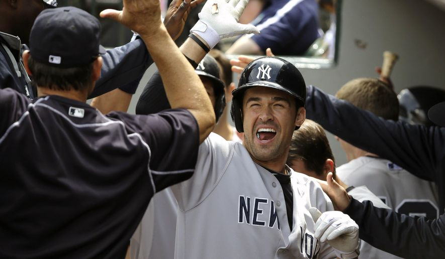 New York Yankees' Garrett Jones is greeted in the dugout after he hit a two-run home run against the Seattle Mariners in the fourth inning of a baseball game, Wednesday, June 3, 2015, in Seattle. (AP Photo/Ted S. Warren)