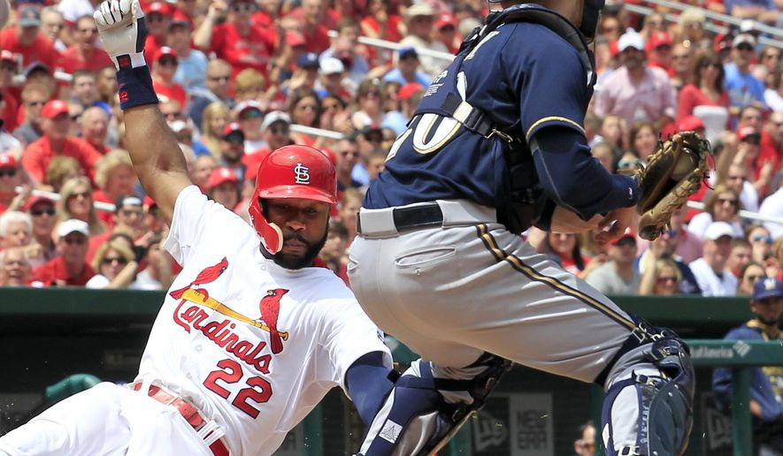 St. Louis Cardinals' Jason Heyward, left, scores ahead of the tag from Milwaukee Brewers catcher Jonathan Lucroy during the fourth inning of a baseball game Wednesday, June 3, 2015, in St. Louis. (AP Photo/Jeff Roberson)