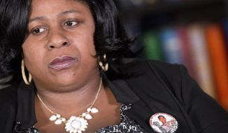 FILE - In this Dec. 15, 2014 file photo, Samaria Rice, of Cleveland, Ohio, wears a button with her son, Tamir Rice,  photograph during an interview at The Associated Press, Monday, Dec. 15, 2014 in New York.  Police say the investigation into the death of Rice, a 12-year-old boy fatally shot by a Cleveland policeman while he held a pellet gun has been turned over to county prosecutors. The Cuyahoga County sheriff's department said Wednesday, June 3, 2015,  its investigation into the shooting of Tamir Rice is complete. The county prosecutor has said the case will be presented to a grand jury that will determine if criminal charges are filed. (AP Photo/Mark Lennihan)