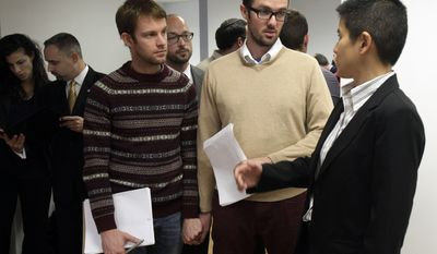 """FILE - In this Tuesday, Nov. 27, 2012 file photo, Christine Sun, right, deputy legal director for the Southern Poverty Law Center, talks with Michael Ferguson, second right, and his partner, Seth Anderson, before a news conference, in New York. Ferguson, of Salt Lake City, is one of four gay men accusing a New Jersey organization of selling """"conversion therapy"""" services promising to make them straight. Instead, they told the news conference that they were subjected to humiliations, including having to strip naked, or taking a baseball bat to effigies of their mothers. (AP Photo/Richard Drew)"""