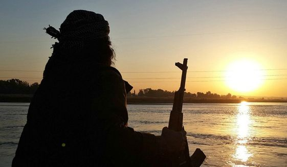 An Islamic State member rests along the Euphrates River in Raqqa, Syria. (Associated Press) ** FILE **
