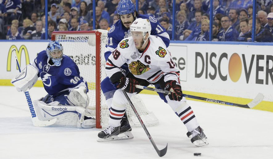 Chicago Blackhawks center Jonathan Toews (19), front, skates around Tampa Bay Lightning center Brian Boyle (11) as goalie Ben Bishop (50), left, defends the net, during the second period in Game 1 of the NHL hockey Stanley Cup Final in Tampa, Fla., Wednesday, June 3, 2015.  (AP Photo/Chris O' Meara)