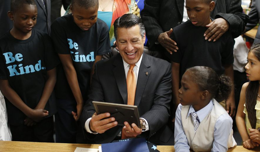 Nevada Governor Brian Sandoval, center, laughs as he looks a picture presented to him by students at Matt Kelly Elementary School during a bill signing ceremony Wednesday, June 3, 2015, in Las Vegas. The ceremony was for Senate Bill 432, which allocates millions of dollars for for low performing schools in the 20 poorest zip codes in Nevada. (AP Photo/John Locher)