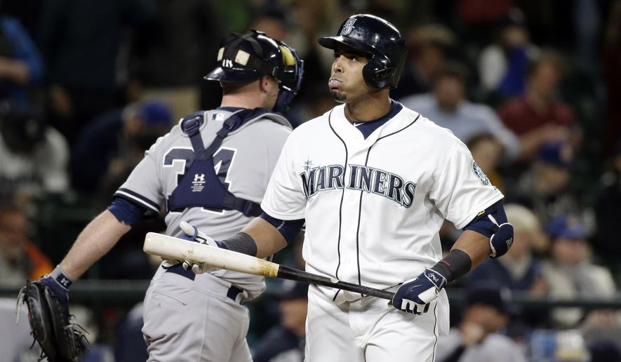 Seattle Mariners' Nelson Cruz, right, heads away from the plate after striking out to end the baseball game in the 11th inning as New York Yankees catcher Brian McCann leaves the field Tuesday, June 2, 2015, in Seattle. The Yankees won 5-3 in 11 innings. (AP Photo/Elaine Thompson)