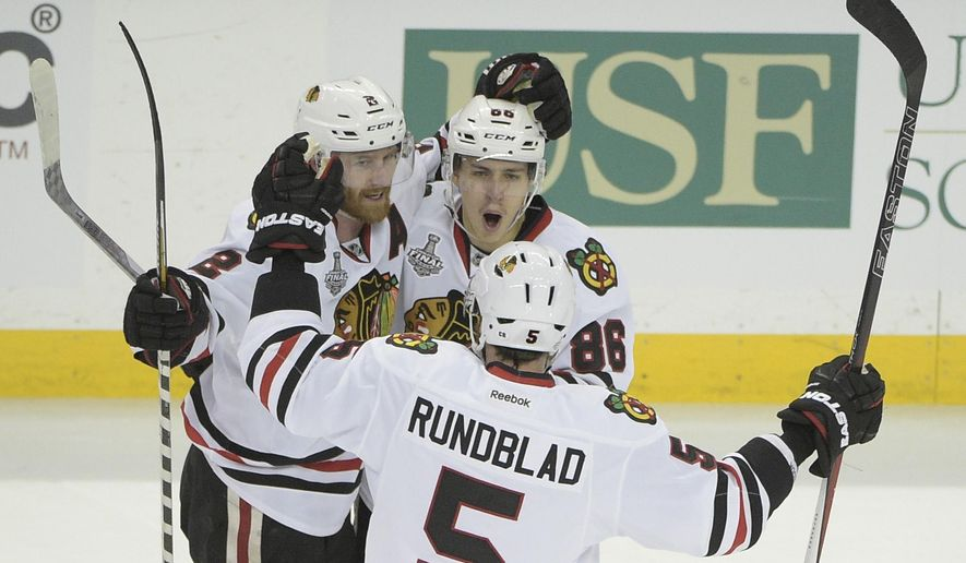 Chicago Blackhawks left wing Teuvo Teravainen (86) of Finland, top right, celebrates his goal with Duncan Keith (2) of Canada, left, and David Rundblad (5) of Sweden, during the third period in Game 1 of the NHL hockey Stanley Cup Final against the Tampa Bay Lightning in Tampa, Fla., Wednesday, June 3, 2015.  The Blackhawks won 2-1. (AP Photo/Phelan M. Ebenhack)