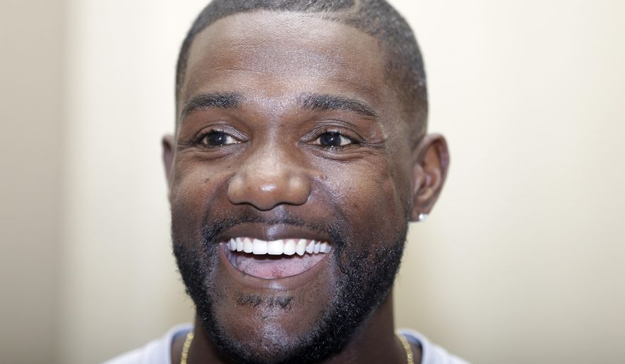 Sprinter Justin Gatlin smiles during a press conference for the Prefontaine Classic track and field meet in Eugene, Ore., Friday, May 29, 2015.  Gatlin will compete in the 200-meter race Saturday. (AP Photo/Don Ryan)