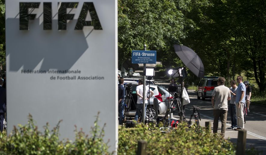 Journalists wait in front of the FIFA logo at the FIFA headquarters in Zurich, Switzerland, Wednesday, June 3, 2015. About 100 journalists outside FIFA headquarters are sunbathing or taking shade from the baking sun, waiting for more news a day after FIFA President Sepp Blatter announced he will resign. (Ennio Leanza/Keystone via AP)
