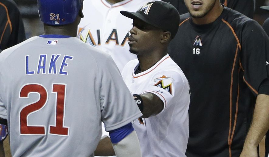 Miami Marlins' Dee Gordon, center, holds back Chicago Cubs' Junior Lake (21) as Lake and Marlins' Jose Fernandez, right, exchange words after Lake hit a home run scoring Anthony Rizzo during the sixth inning of a baseball game, Wednesday, June 3, 2015, in Miami. Lake gestured at the Miami dugout during his home run trot, which inspired a bench-clearing confrontation led by Fernandez. Surrounded by their teammates, Lake and Fernandez screamed at each other near home plate before they were pulled away toward their respective dugouts. No one was ejected. (AP Photo/Wilfredo Lee)