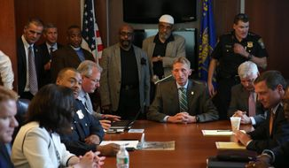 Community members and police officials at Boston Police Department Headquarters prepare to see video, Wednesday, June 3, 2015, in Boston, of a fatal police shooting on Tuesday, in the city's Roslindale neighborhood. Police said the video shows that officers did not have their weapons drawn when they approached Usaama Rahim and that they backed up when he initially lunged at them with a knife. (David Ryan/The Boston Globe via AP, Pool)